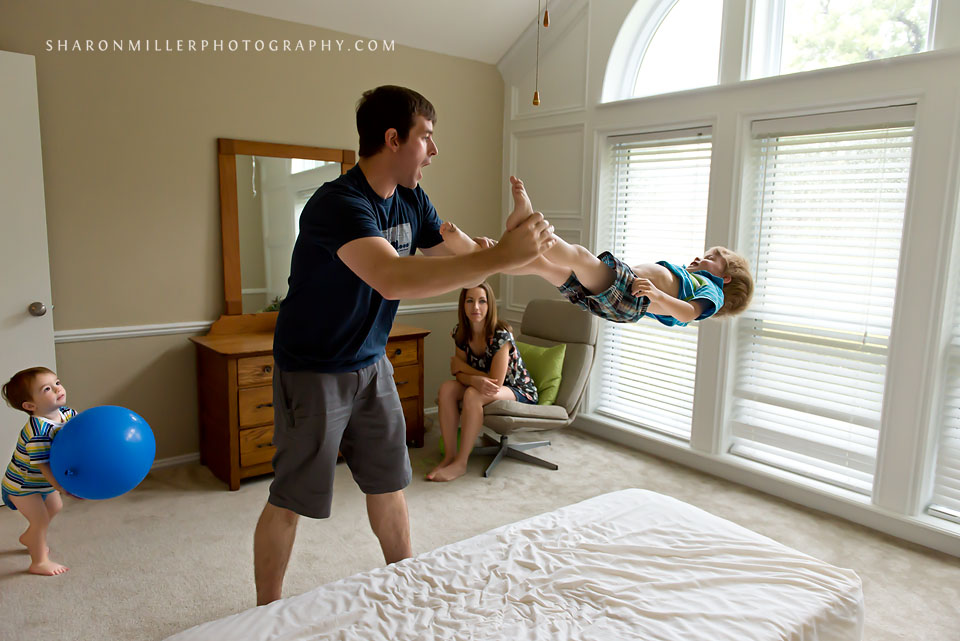 dad swinging happy boy by ankles during Flower Mound family documentary session