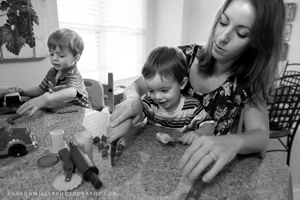 black and white photo of mom playing with playdoh with sons during Flower Mound family documentary session