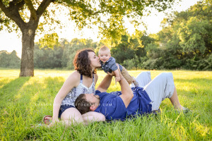 photo of Mom kissing baby being held up by Daddy under a tree
