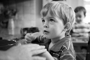 boy eating an apple at the kitchen counter