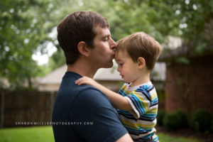 dad holding toddler son kissing him on the forehead
